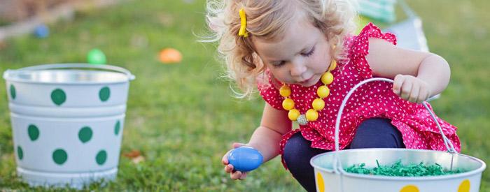 bambina con vestito rosa che raccoglie uova di cioccolato nel prato